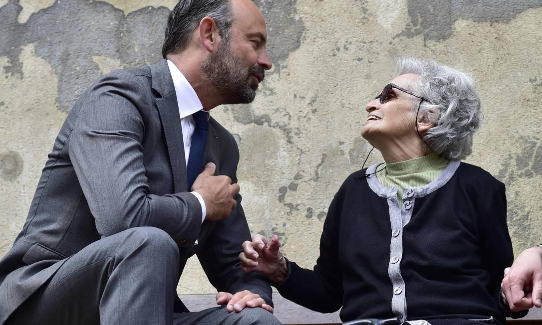 O primeiro-ministro francês, Edouard Philippe, fala com uma idosa em frente à igreja Saint Jacques em Aubeterre-sur-Dronne, perto de Angoulême, no oeste da França, no segundo dia de sua visita à região de Charente Foto: GEORGES GOBET / AFP