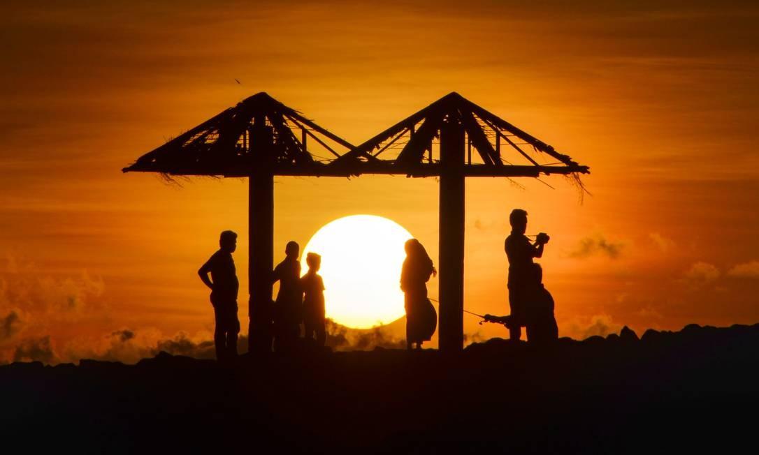 Indonésios apreciam o pôr do sol na praia de Lhoknga, na província de Aceh Foto: CHAIDEER MAHYUDDIN / AFP
