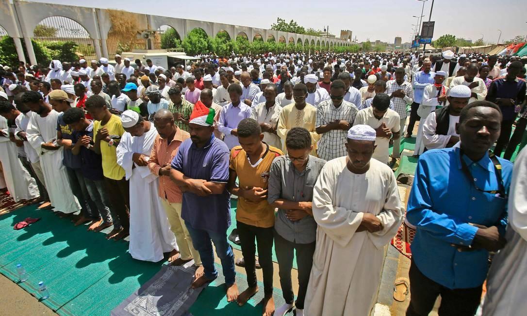 Manifestantes sudaneses se reúnem durante as orações do meio-dia de sexta-feira em frente ao quartel-general do Exército em Cartum, enquanto continuam a protestar exigindo que o conselho militar governante entregue o poder a uma administração civil Foto: ASHRAF SHAZLY / AFP