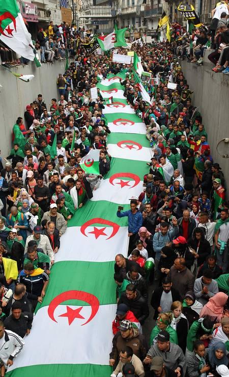 Manifestantes argelinos participam de uma manifestação contra o governo na capital do país, Argel. Os argelinos se reuniram para a 11ª sexta-feira consecutiva de manifestações, a última antes do início do Ramadã, durante o qual pretendem continuar protestando Foto: - / AFP