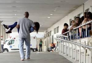 Mauro Faustino, funcionário da empresa Redentor, chega ao Souza Aguiar com Priscila nos braços: passageira passou mal em ônibus da linha 390 (Curicica-Candelária) Foto: Guilherme Pinto / Agência O Globo