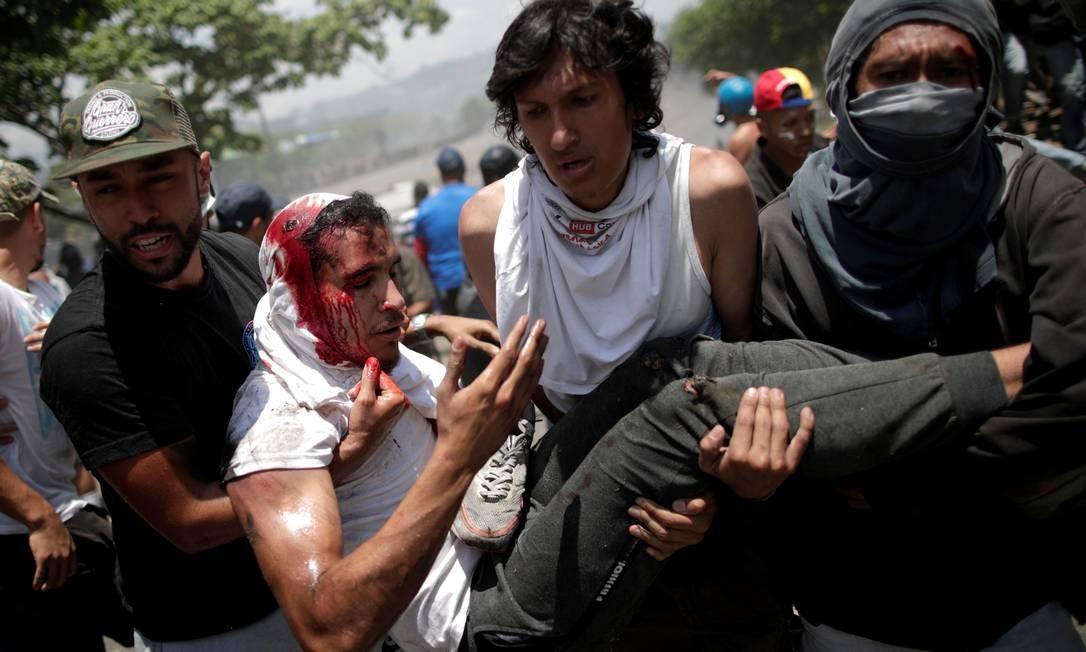 8876226d3 O opositor Luis Alejandro é carregado por manifestantes após ser ferido em  protesto perto da base