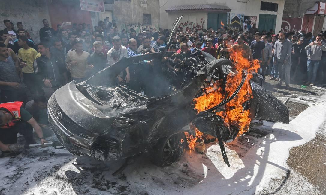 Serviços de emergência palestinos tentam apagar chamas de carro de chefe do Hamas, atingido por bombardeio israelense, em Gaza Foto: MAHMUD HAMS 05-05-2019 / AFP