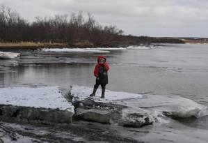 Criança brinca sobre gelo derretido após erosão de permafrost no Alasca; segundo cientistas, a região está aquecendo duas vezes mais rápido que a média global Foto: Mark RALSTON/AFP/18-4-2019