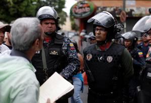 Cidadão entrega documento a guarda nacional perto de base militar em Caracas, na Venezuela Foto: STRINGER / REUTERS