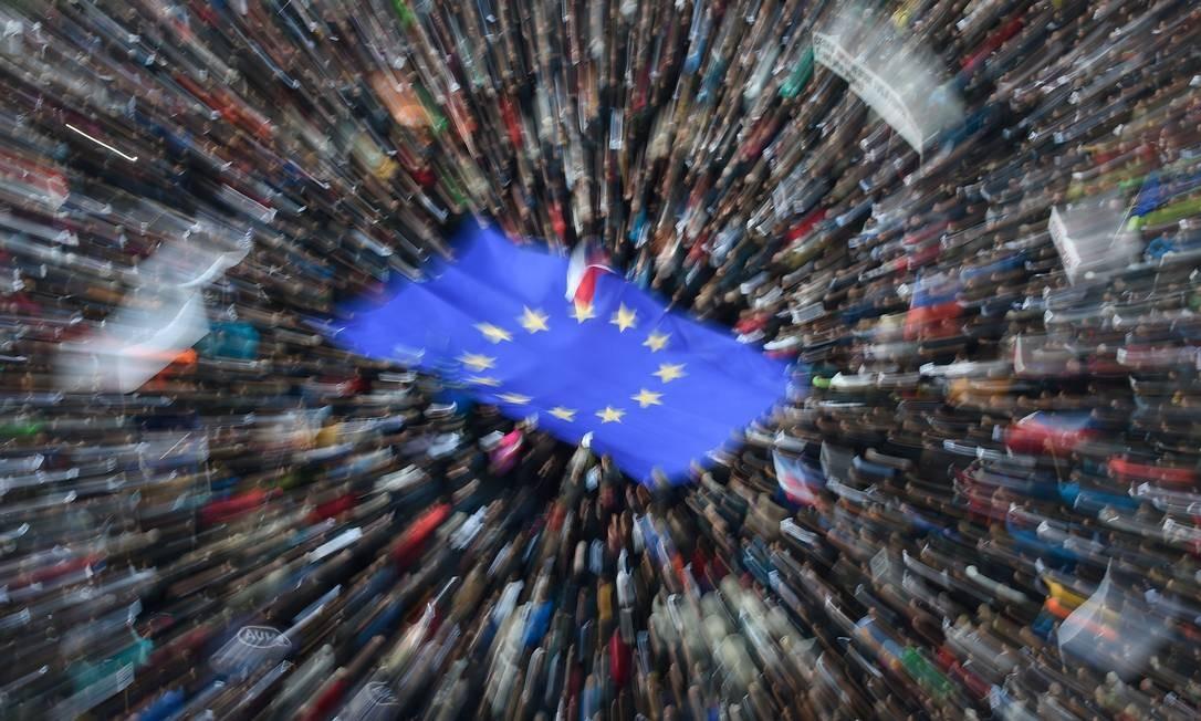 Em Praga, capital da República Tcheca, manifestantes agitam uma gigantesca bandeira europeia durante um protesto na Praça da Cidade Velha contra a nomeação de Marie Benesova para o Ministério da Justiça, por ser muito próxima do primeiro-ministro, o bilionário Andrej Babis, acusado de fraude de subsídio da União Europeia. Foto: MICHAL CIZEK / AFP