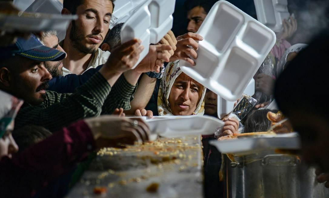 Muçulmanos fazem fila por comida para quebrar seu jejum em Diyarbakir, no sudeste da Turquia, no primeiro dia do mês sagrado do Ramadã. Foto: ILYAS AKENGIN / AFP