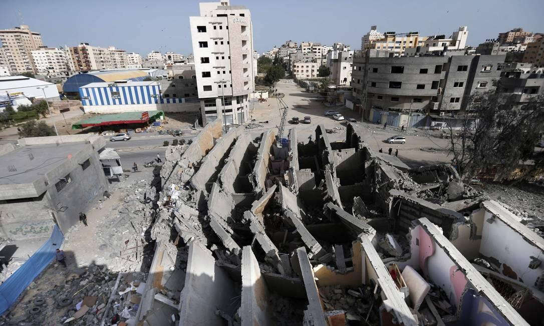 Um edifício na cidade de Gaza foi destruído durante os ataques aéreos israelenses. Líderes palestinos em Gaza concordaram com um cessar-fogo com Israel para acabar com uma escalada letal de dois dias na violência que ameaçava ampliar a guerra, informaram autoridades com conhecimento do acordo. Foto: MAHMUD HAMS / AFP