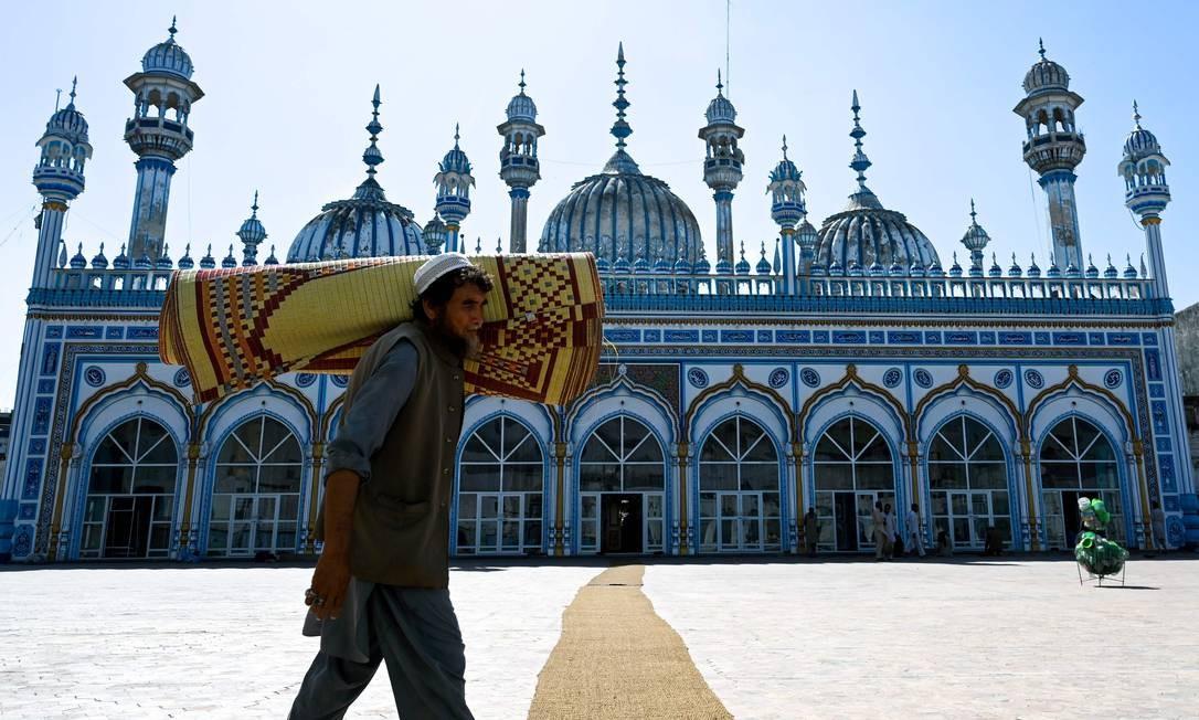 Um muçulmano paquistanês carrega uma esteira de oração enrolada em seu ombro em preparação para as orações especiais da noite em Rawalpindi, antes do início do mês sagrado de jejum do Ramadã. Os muçulmanos estão se preparando para o mês sagrado do Ramadã, que é calculado com o avistamento da lua nova e durante o qual eles jejuam desde o amanhecer até o anoitecer. Foto: AAMIR QURESHI / AFP