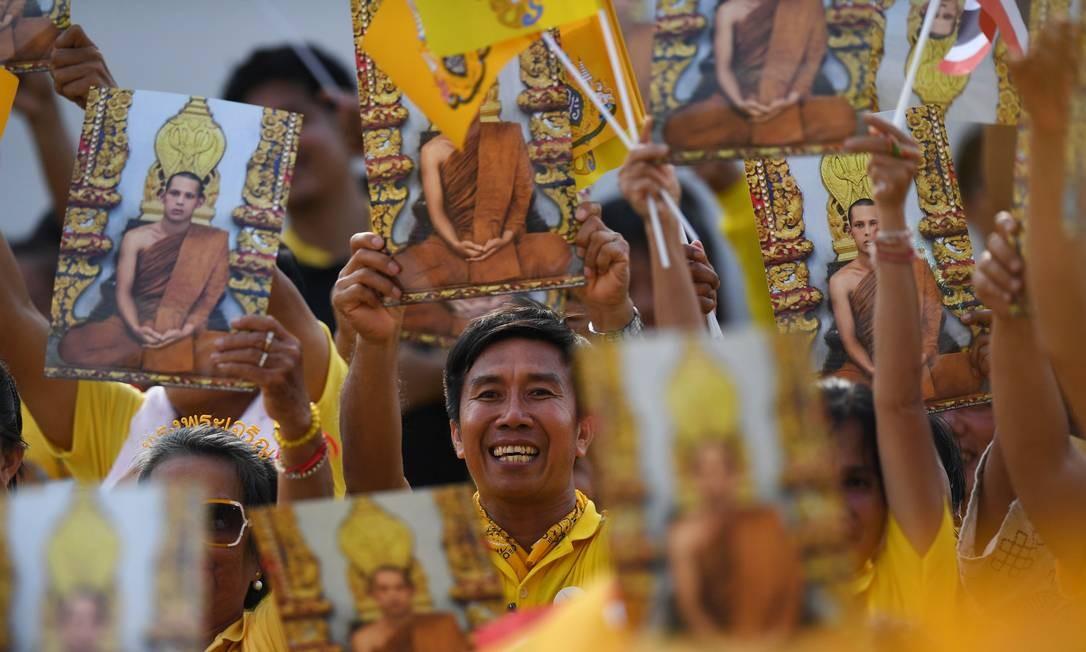 Pessoas seguram retratos do rei da Tailândia, Maha Vajiralongkorn, enquanto esperam por ele e pela rainha Suthida aparecerem na sacada do Salão Suddhaisavarya Prasad, do Grande Palácio, para conceder audiência pública no último dia de sua coroação real em Bangkok. Foto: LILLIAN SUWANRUMPHA / AFP