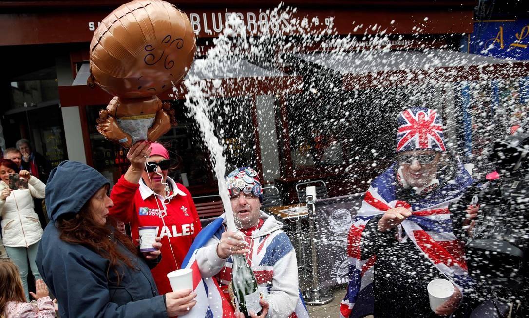 John Loughery, um fanático pela realeza britânica, estoura um espumante próximo ao Castelo de Windsor, na região oeste de Londres. A celebração se seguiu ao anúncio de que a Duquesa de Sussex, Meghan Markle, deu à luz seu filho com o príncipe Harry. Foto: ADRIAN DENNIS / AFP