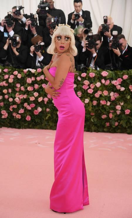 O tubinho rosa pink, todo colado ao corpo, foi um dos looks que a cantora usou na entrada do baile Foto: Neilson Barnard/AFP