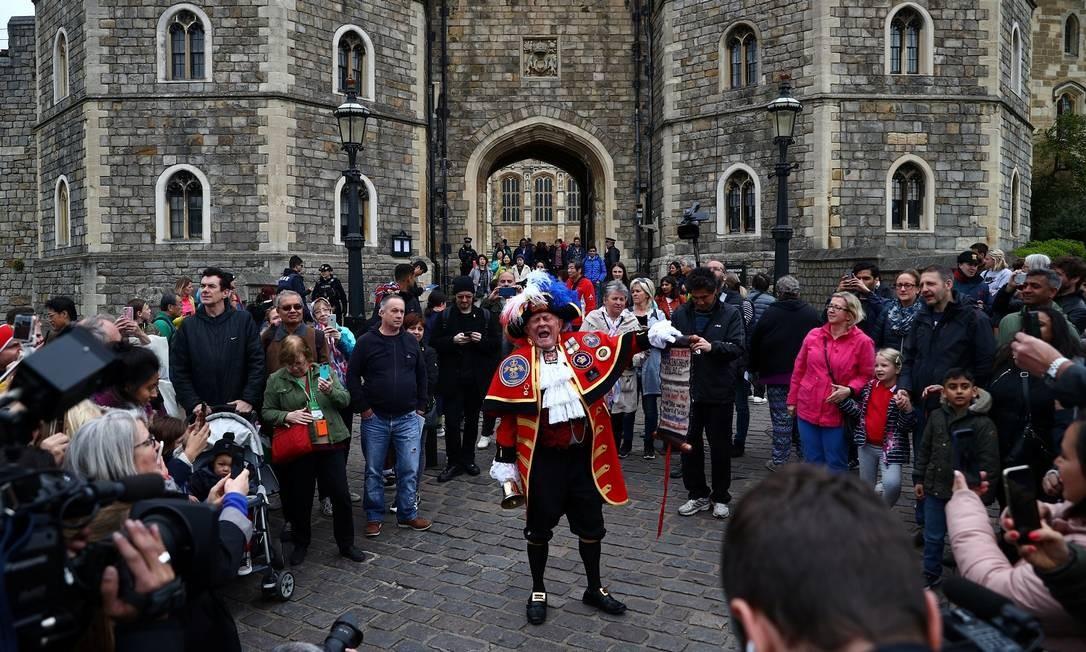 Homem vestido com uma fantasia que remete à realeza faz anúncio do lado de fora do Castelo de Windsor Foto: HANNAH MCKAY / REUTERS