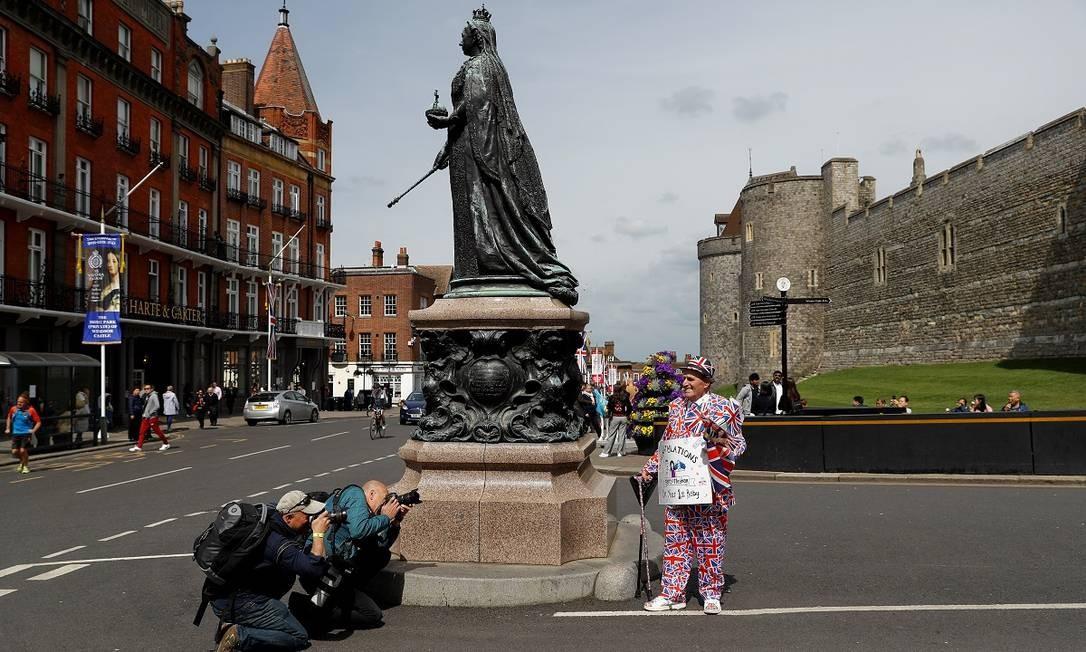 Aos pés da estátua da rainha Vitória, em frente ao castelo de Windsor, um fã da família real celebra o nascimento do filho de Harry e Meghan Foto: PETER NICHOLLS / REUTERS