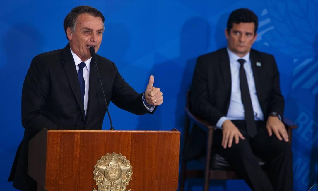 O presidente Bolsonaro e o ministro da Justiça Sergio Moro durante evento que marcou a assinatura do decreto com modificações nas regras para o porte de armas Foto: Daniel Marenco / O Globo