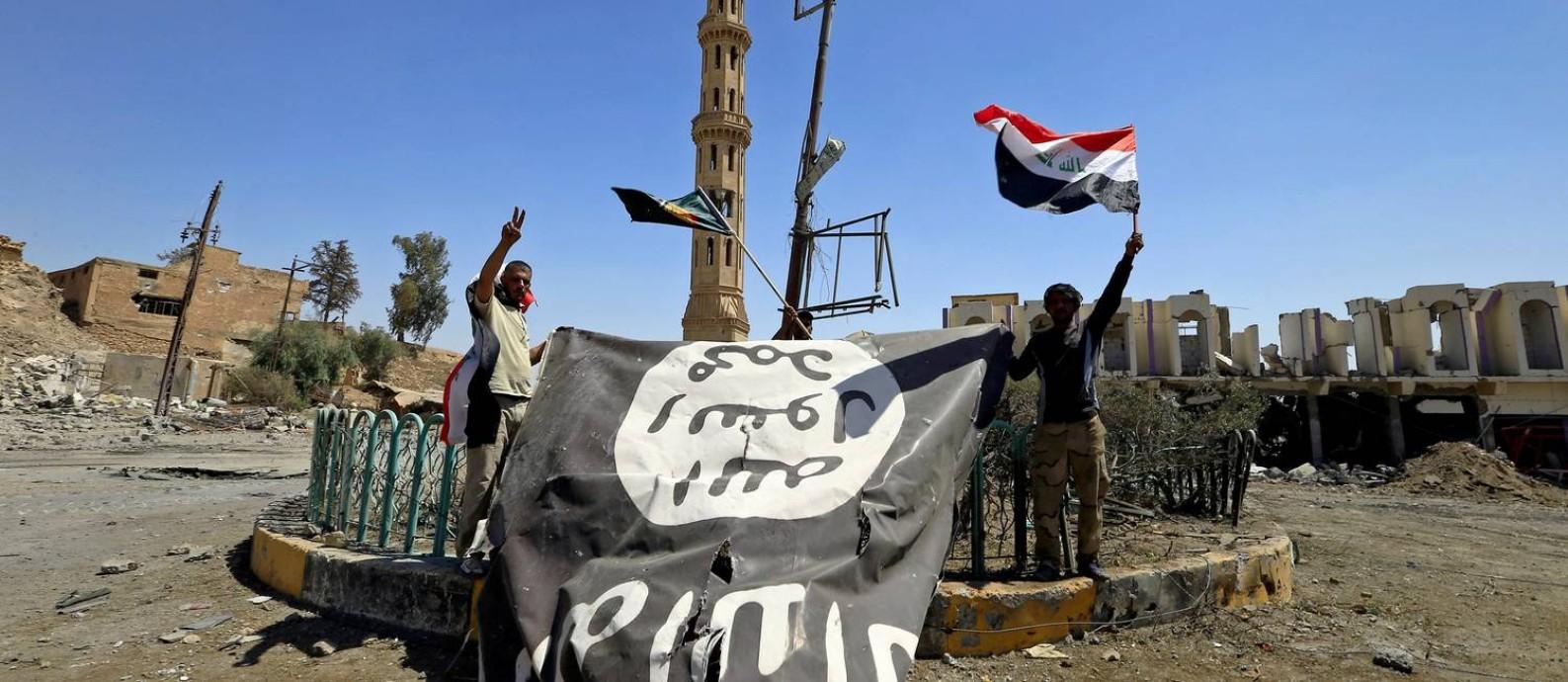06c2f7b6e4 Integrantes das Forças de Mobilização Popular seguram bandeira do Estado  Islâmico após derrotar extremistas em Tal
