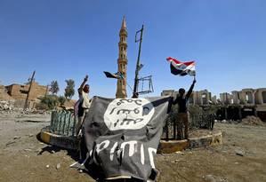 Integrantes das Forças de Mobilização Popular seguram bandeira do Estado Islâmico após derrotar extremistas em Tal Afar, no Iraque Foto: Thaier Al-Sudani 27-08-2017 / REUTERS