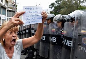 """Mulher protesta contra governo de Nicolás Maduro em frente a agentes da Polícia Nacional Bolivariana (PNB) na capital, Caracas; ela carrega papel no qual se lê: """"amigo, você que defende um governo corrupto, apegue-se à Constituição"""" Foto: JUAN BARRETO / AFP/04-05-2019"""