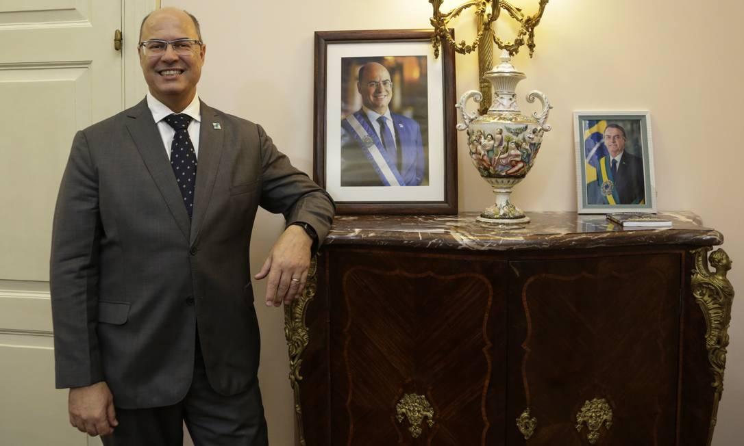 Witzel posa ao lado de móvel com sua foto oficial e do presidente Jair Bolsonaro, no Palácio Guanabara Foto: Marcos Ramos / Agência O Globo - 28/03/2019