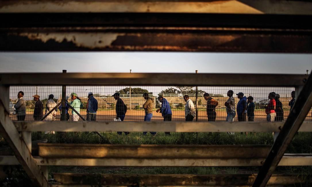 Pessoas fazem fila para votar no distrito de Kwamashu, nos arredores de Durban, durante a sexta eleição geral na África do Sul Foto: MARCO LONGARI / AFP