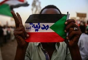 Manifestante sudanês segura a bandeira do país com os dizeres 'apenas civis' escritos em árabe em protesto do lado de fora da sede do Ministério da Defesa em Cartum: pressão por novo conselho de transição com participação civil Foto: ASHRAF SHAZLY/AFP/02-05-2019