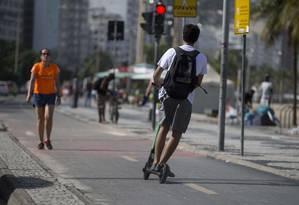 Usuário faz zigue-zagues com patinete na orla de Copacabana Foto: Márcia Foletto / Agência O Globo