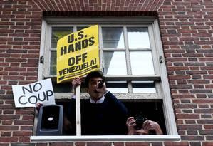 Manifestante protesta com placa que tem palavras de ordem contra a intervenção americana na Venezuela Foto: CLODAGH KILCOYNE / REUTERS