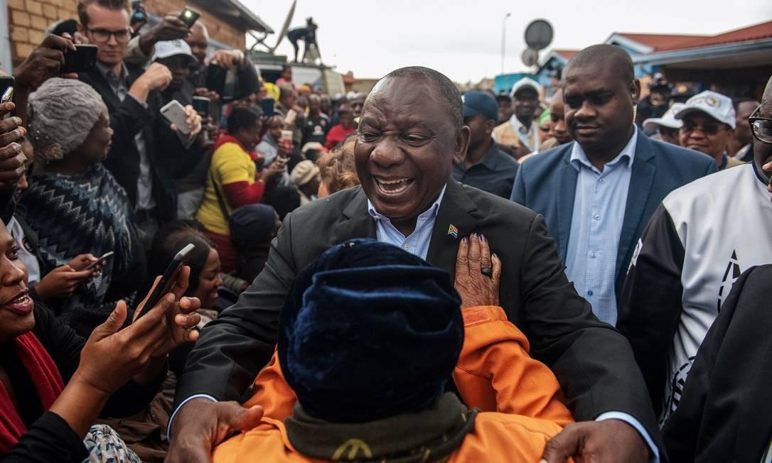 Presidente Cyril Ramaphosa, do Congresso Nacional Africano, cumprimenta eleitores ao chegar para votar em Soweto Foto: MICHELE SPATARI / AFP/08-05-2019