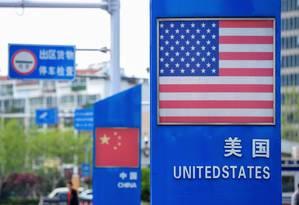 Bandeiras da China e dos EUA na zona frana do porto de Qingdao, no leste do país asiático. Foto: STR / AFP