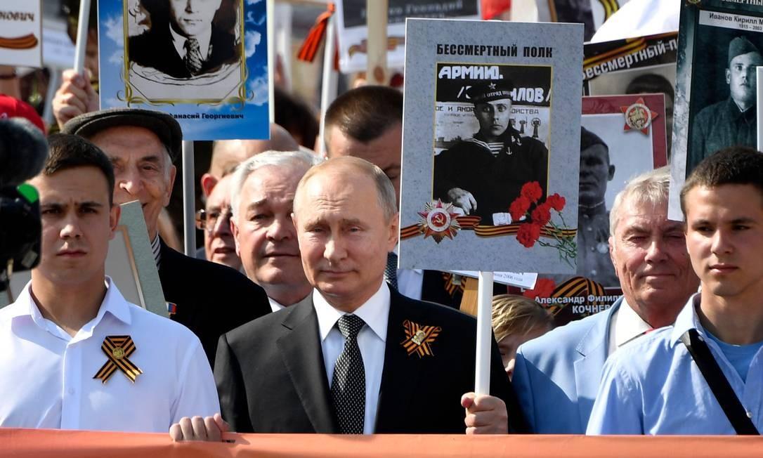O presidente russo Vladimir Putin e outros participantes trazem retratos de seus parentes — soldados da Segunda Guerra Mundial — enquanto participam da marcha do Regimento Imortal na Praça Vermelha, no centro de Moscou. A Rússia celebra o 74º aniversário da vitória sobre a Alemanha nazista Foto: ALEXANDER NEMENOV / AFP