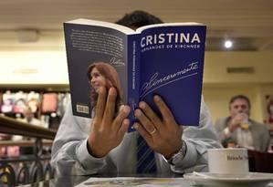 Homem lê um cópia de 'Sinceramente', livro da ex-presidente argentina Cristina Kirchner, num café no centro de Buenos Aires Foto: JUAN MABROMATA / AFP