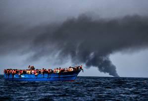 Migrantes esperam para serem resgatados no Mediterrâneo em 2016 Foto: ARIS MESSINIS / AFP
