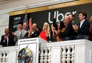 CEO da Uber, Dara Khosrowshah (de terno preto batendo palma) comemora após tocar o sino de abertura da sessão da Bolsa de Nova York Foto: ANDREW KELLY/REUTERS
