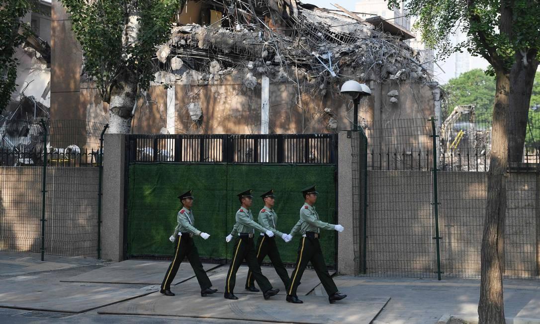 Militares chineses passem em frente à antiga embaixada americana em Pequim, que está sendo demolida vinte anos após ser destruída em protestos em maio de 1999. O protesto aconteceu após os Estados Unidos bombardearem a embaixada chinesa em Belgrado, Sérvia, matando três jornalistas chineses. Milhares foram às ruas protestar o ato. Foto: GREG BAKER / AFP
