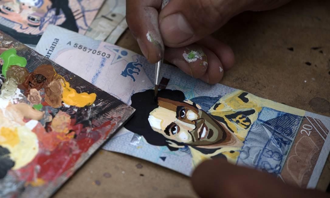 O migrante venezuelano Javier Ceballos pinta uma nota de Bolívar com a imagem do traficante colombiano Pablo Escobar para protestar contra a situação econômica na Venezuela Foto: IVAN VALENCIA / AFP