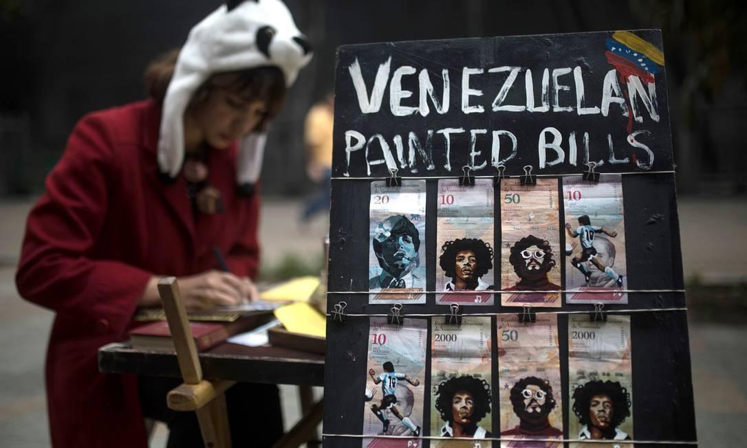 A migrante venezuelana Paula Villamizar pinta notas de Bolívares para ganhar dinheiro Foto: IVAN VALENCIA / AFP