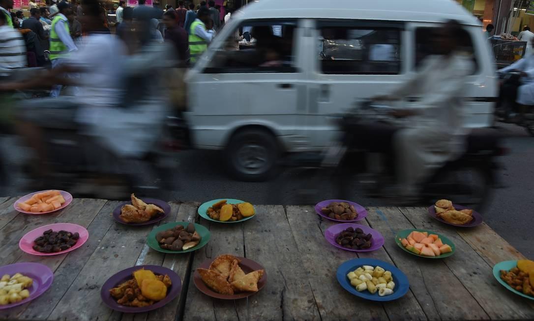 Paquistâneses passam por pratos de comida iftar. Essas refeições são feitas especialmente para as pausas no jejum do Ramadã, que acontece do nascer ao por do sol durante o mês sagrado do islamismo Foto: ASIF HASSAN / AFP