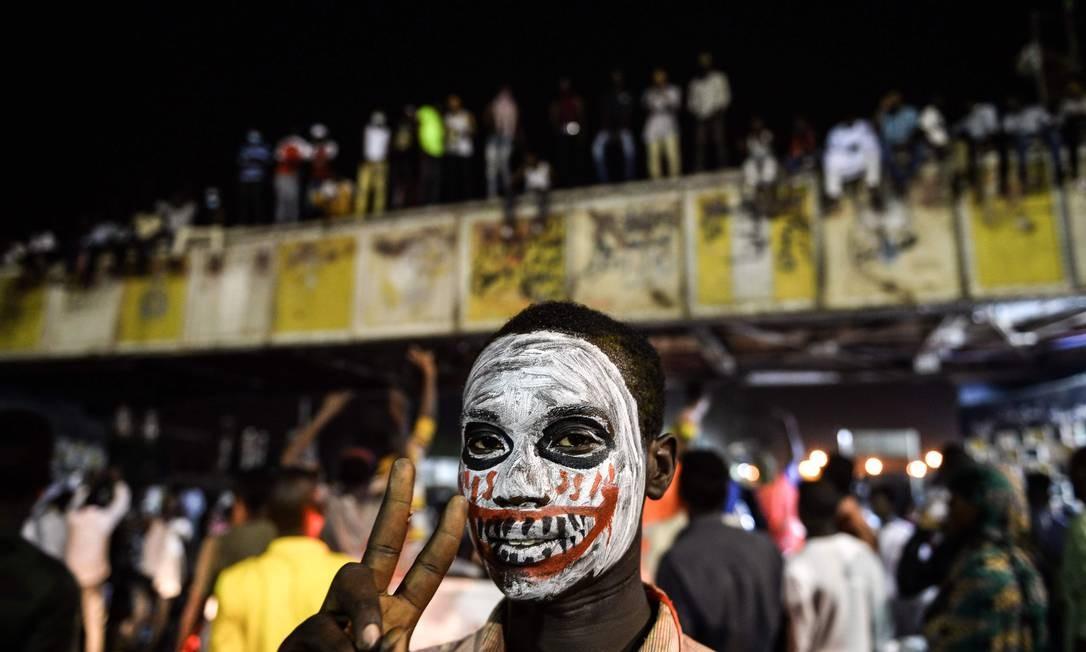 Um manifestante sudanês celebra uma vitória do lado de fora de um quartel na cidade de Khartoum Foto: MOHAMED EL-SHAHED / AFP