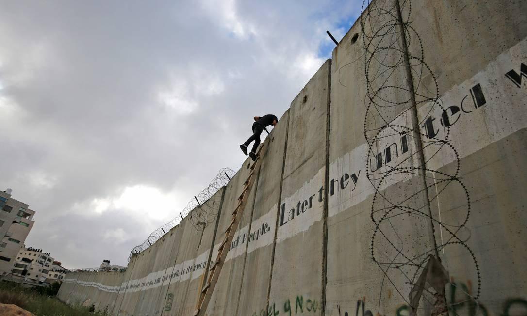 Jovens palestinos escalam um trecho da muralha que separa Israel da Palestina para poderem chegar à mesquita al-Aqsa Foto: ABBAS MOMANI / AFP