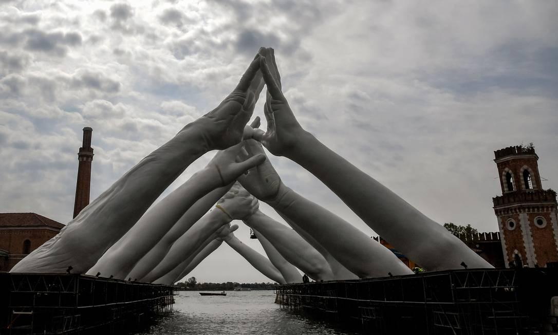 'Building bridges', instalação do iataliano Lorenzo Quinn, na qual seis pares de braços se tocam sobre um canal no Arsenal Foto: TIZIANA FABI / AFP