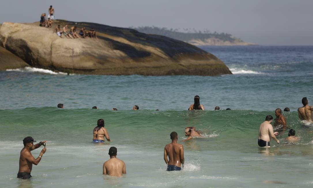 As pedras e o mar do Arpoador ficam cheios de banhistas no outono quente Foto: Gabriel de Paiva / Agência O Globo