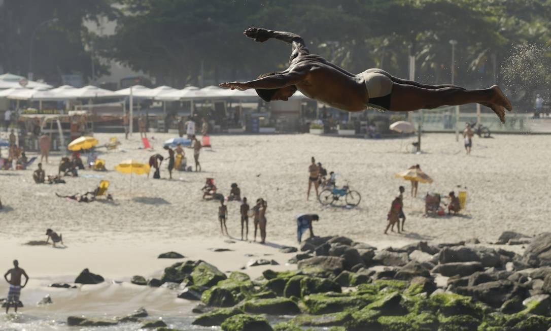 Um homem salta do Caminho do Pescador, no Leme Foto: Gabriel de Paiva / Agência O Globo