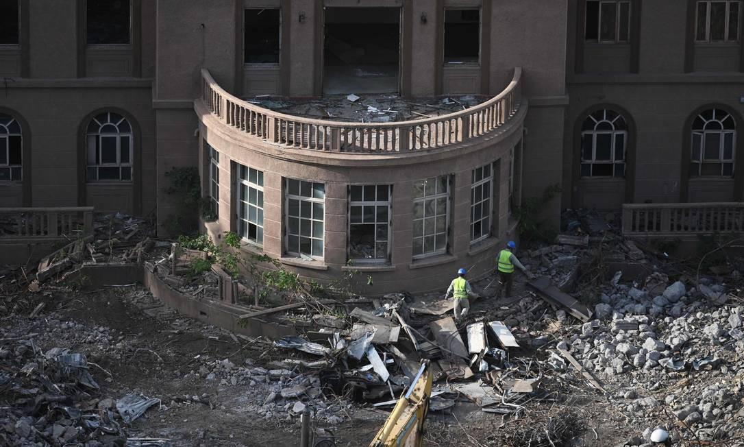 Trabalhadores caminham no local de demolição da antiga embaixada dos EUA em Pequim. A antiga embaixada está sendo demolida, 20 anos depois de ter sido atacada por manifestantes chineses. Os protestos, em 8 de maio de 1999, ocorreram um dia depois que as forças dos EUA atingiram a embaixada chinesa em Belgrado, durante uma campanha de bombardeio da Otan, matando três jornalistas chineses. Milhares de chineses se reuniram nas ruas do entorno da embaixada dos EUA por dois dias, muitos atirando pedras de pavimentação e tentando invadir a embaixada. Foto: GREG BAKER / AFP