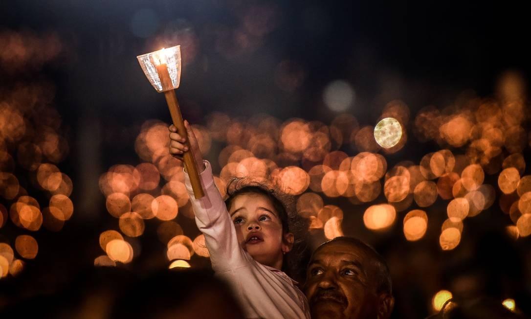 Uma criança segura uma vela durante uma procissão no santuário de Fátima, em Fátima, no centro de Portugal, em 12 de maio. Foto: PATRICIA DE MELO MOREIRA / AFP