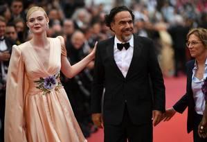 Alejandro Gonzalez Iñárritu com a atriz Elle Fanning e a diretora Kelly Reichardt, que fazem parte do júri presidido pelo mexicano Foto: LOIC VENANCE / AFP