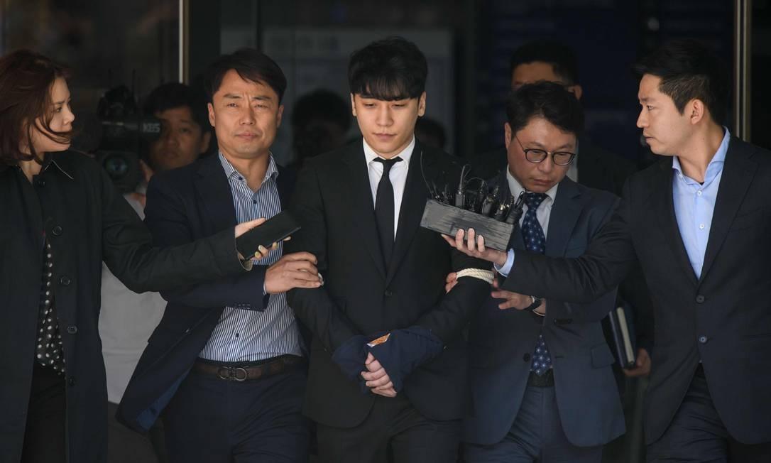 Ex-integrante da boyband BIGBANG, Lee Seung-hyun é levado sob custódia ao deixar o Supremo Tribunal em Seul. O rapaz de 28 anos está ligado a uma investigação policial sobre Burning Sun, uma boate na qual ele era diretor de relações públicas, onde supostamente filmavam mulheres com câmeras escondidas e usavam álcool e drogas para atacá-las sexualmente Foto: ED JONES / AFP