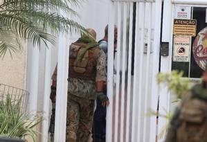 Dois militares durante negociação com homem que mantém mulher e filhos reféns dentro de apartamento em Cascadura Foto: Fabiano Rocha / Agência O Globo