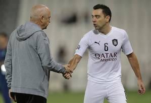 Xavi cumprimenta o técnico do Al Sadd, Jesualdo Ferreira Foto: KARIM JAAFAR / AFP