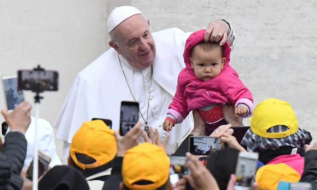Papa Francisco acaricia um bebê ao chegar para sua audiência geral semanal na Praça de São Pedro, no Vaticano Foto: VINCENZO PINTO / AFP