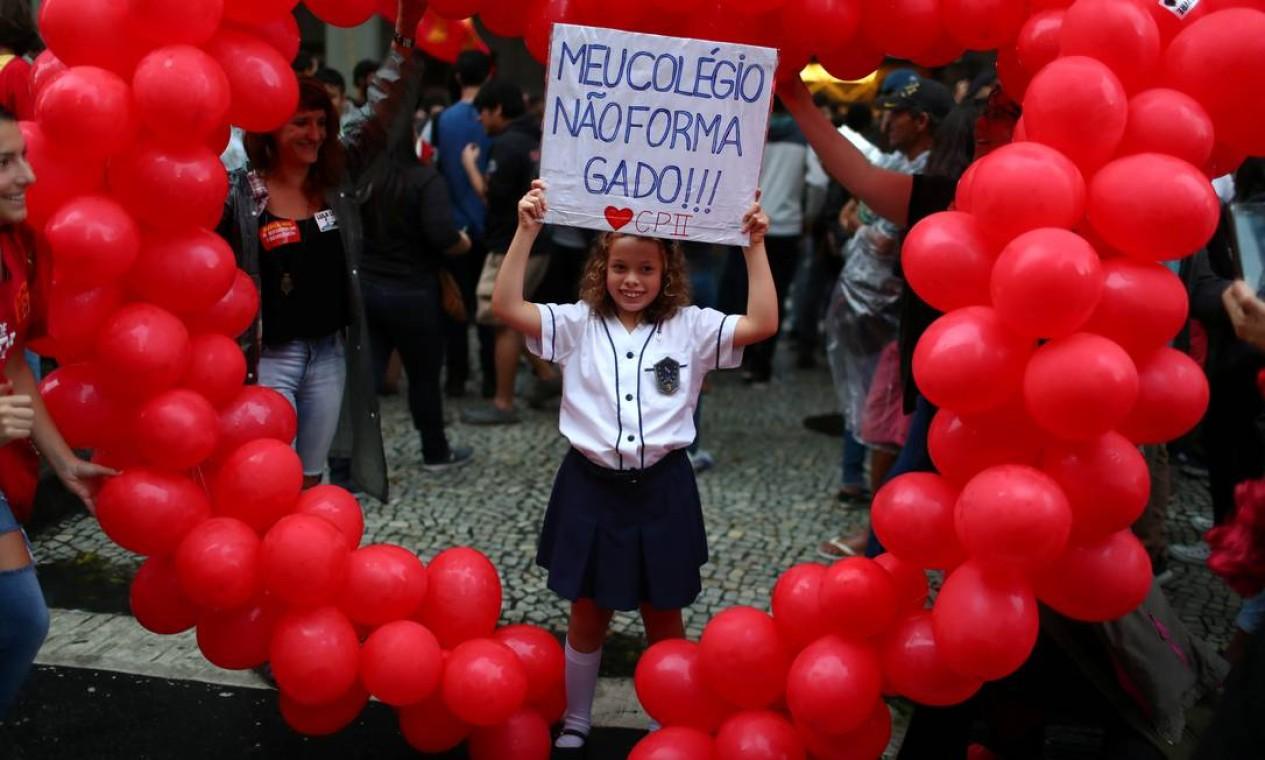 """Com cartaz, """"Meu colégio não forma gado"""", menina critica cortes orçamentários feitos pelo MEC Foto: PILAR OLIVARES / REUTERS"""